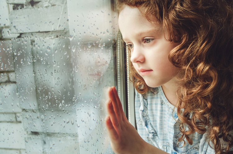 Sad child looking out window - What do you tell a child who is dying of a terminal disease?