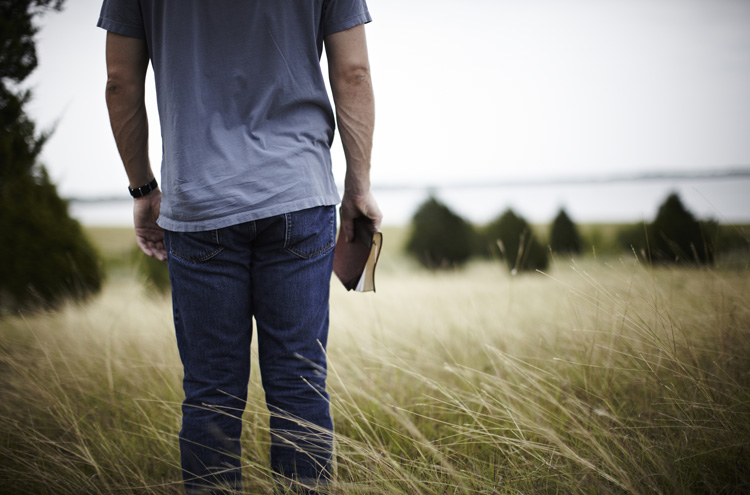 Man holding Bible, looking into distance - What part do good works play in your salvation?