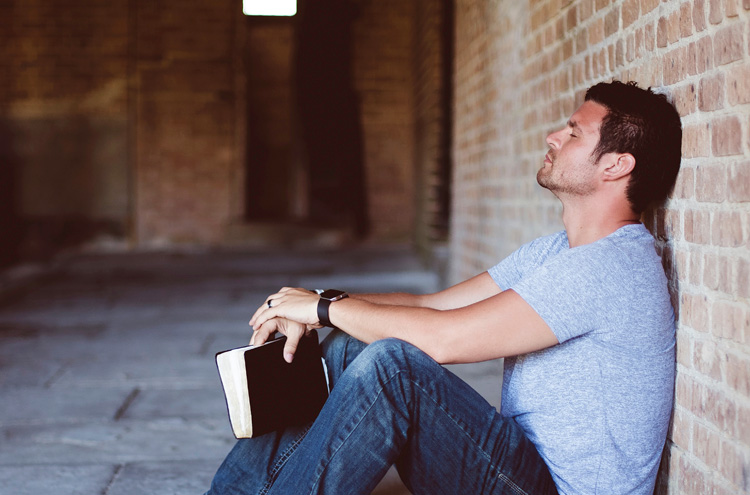 Man resting against wall with Bible - should you keep the sabbath