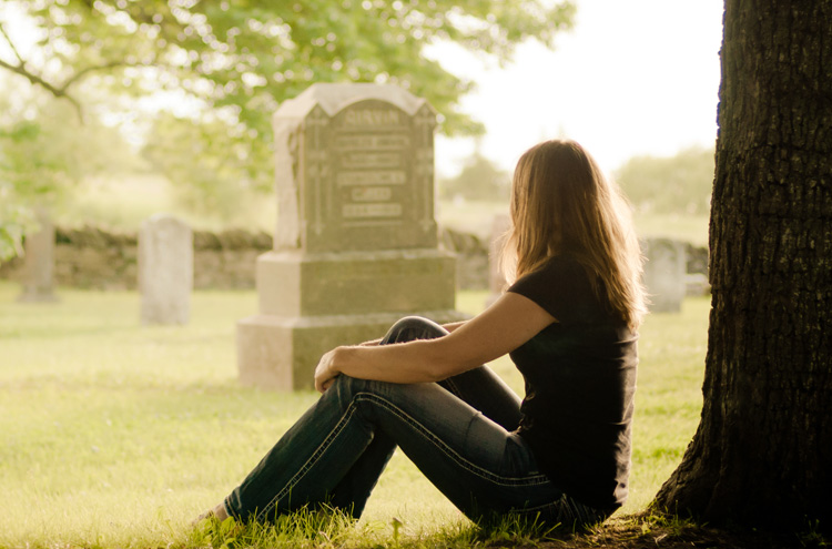 Woman sitting against tree, looking at a graveyard - What happens when you die?