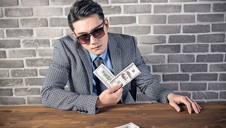 Greedy businessman holding money - Are all rich people inherently evil?