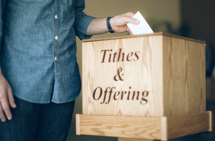 Man putting envelope in Tithes and Offering box - Do you have to tithe?