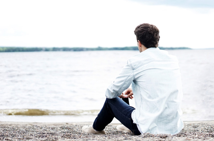 Man sitting by water, reflecting - Can true Christians have addictions?