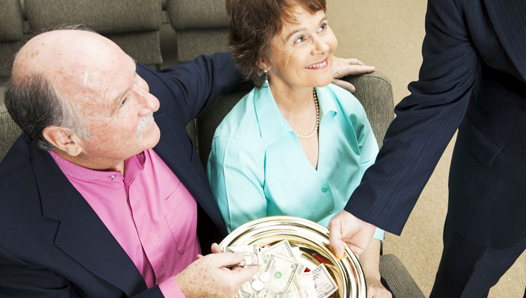 Couple placing money into offering plate - Is tithing to the local church a form of giving or paying
