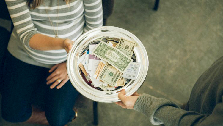 Man passing offering plate - Does the tithe belong to the local church?