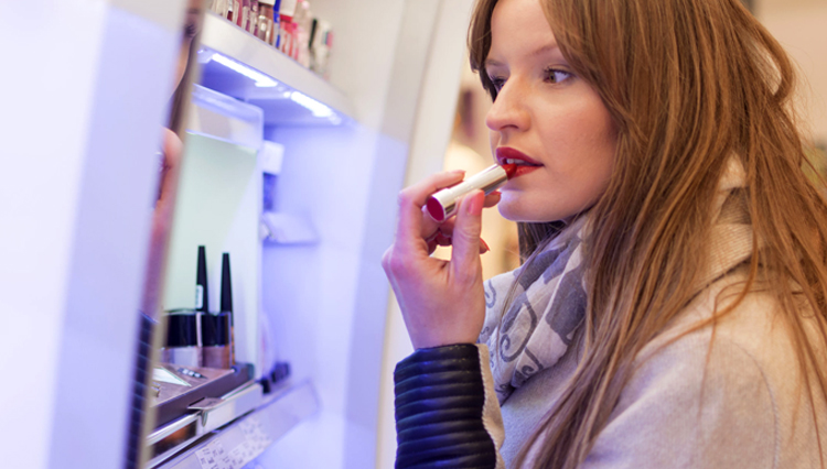 Woman putting on lipstick - Is it wrong for women to wear makeup?