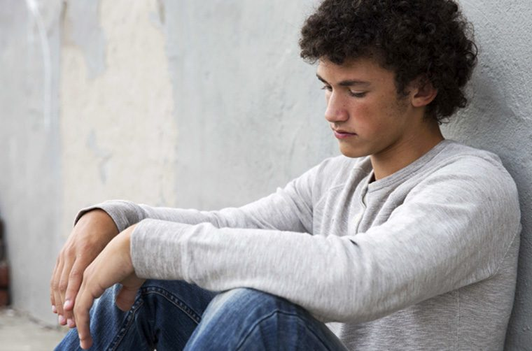 Young man with back to wall, feeling guilty over sin