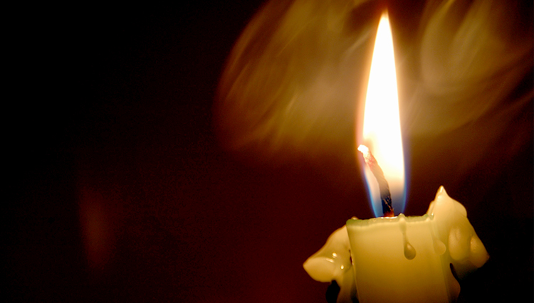 Picture of candle shining in the darkness