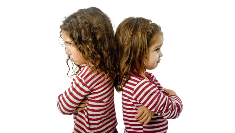 Picture of girls with backs turned against each other, representative of believers upset with each other