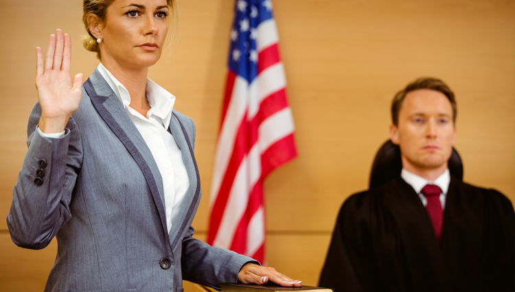 Woman swearing in court, with hand on Bible
