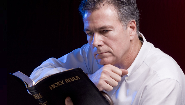 Picture of man reading Bible, thinking
