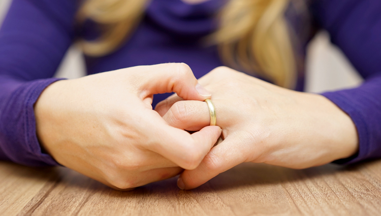 Picture of woman taking wedding ring off finger - symbolic of divorce