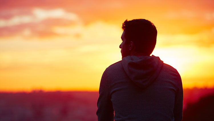 Picture of man looking at sunset, reflecting on motives
