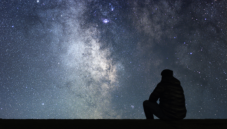 Man looking at the universe, thinking about forever