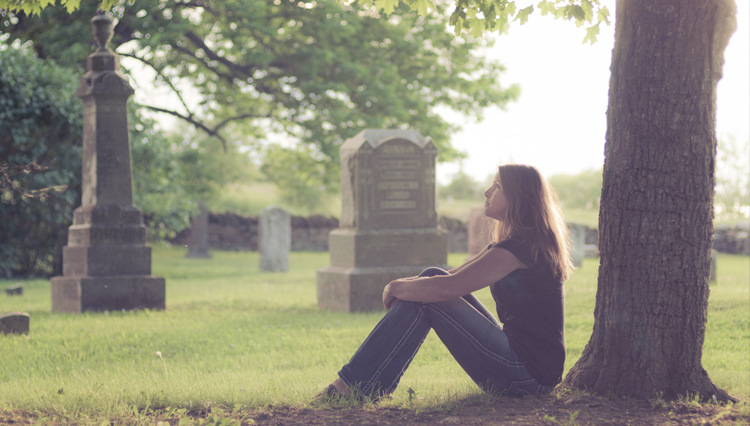 Woman sitting in graveyard, thinking about forgiveness, Heaven, and Hell