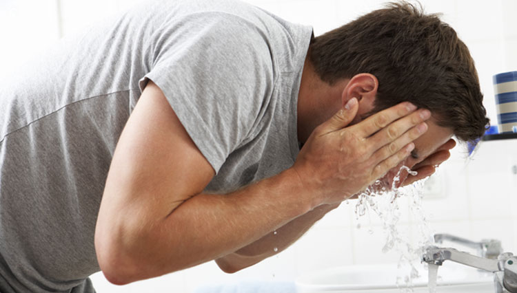 Picture of man washing his face
