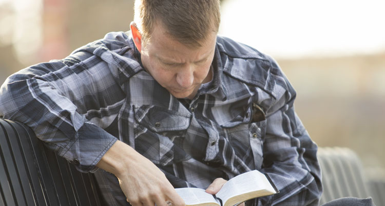 Man wondering if it's God's will for him to be healed, reading Bible
